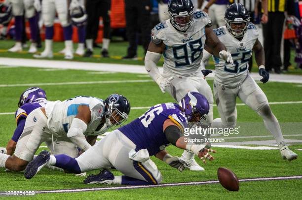 Garrett Bradbury of the Minnesota Vikings scrambles for the ball after a fumbled snap in the fourth quarter of the game agains the Tennessee Titans...