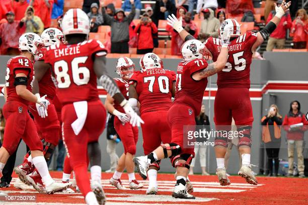 Garrett Bradbury of the North Carolina State Wolfpack celebrates with teammates following a oneyard touchdown run against the East Carolina Pirates...