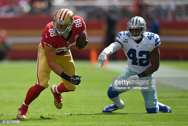 Garrett Celek of the San Francisco 49ers breaks the tackle of Barry Church of the Dallas Cowboys during the first half of their NFL football game at...