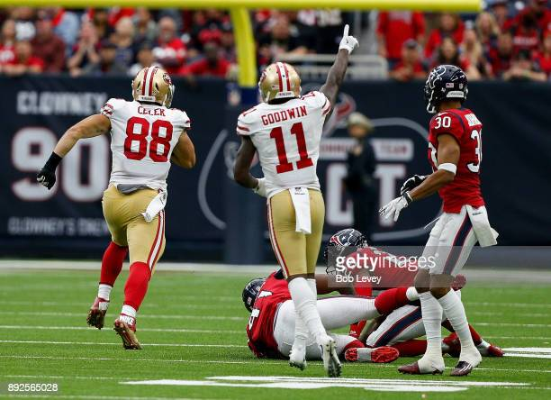 Garrett Celek of the San Francisco 49ers runs with the ball after a pass as Kareem Jackson of the Houston Texans and Andre Hal pursue at NRG Stadium...