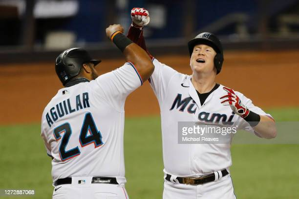 Garrett Cooper of the Miami Marlins celebrates with Jesus Aguilar after hitting a 2-run home run during the first inning off Mike Kickham of the...