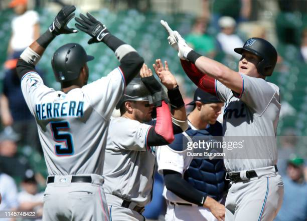 Garrett Cooper of the Miami Marlins right celebrates his grand slam against the Detroit Tigers with Rosell Herrera and Miguel Rojas during the ninth...