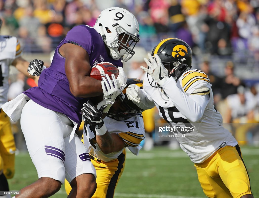 Garrett Dickerson #9 of the Northwestern Wildcats is hit after a catch by Amani Hooker #27 and Joshua Jackson #15 of the Iowa Hawkeyes at Ryan Field on October 21, 2017 in Evanston, Illinois.