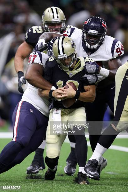 Garrett Grayson of the New Orleans Saints is sacked by Rickey Hatley of the Houston Texans at MercedesBenz Superdome on August 26 2017 in New Orleans...