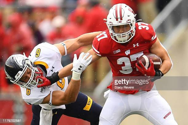 Garrett Groshek of the Wisconsin Badgers avoids a tackle by Matt Bahr of the Kent State Golden Flashes during the first half at Camp Randall Stadium...