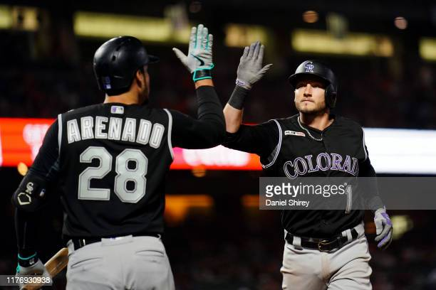 Garrett Hampson celebrates a solo home run with Nolan Arenado of the Colorado Rockies during the eighth inning against the San Francisco Giants at...