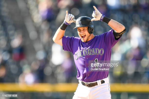 Garrett Hampson of the Colorado Rockies celebrates after hitting a 10th inning walkoff sacrifice single to defeat the Miami Marlins at Coors Field on...