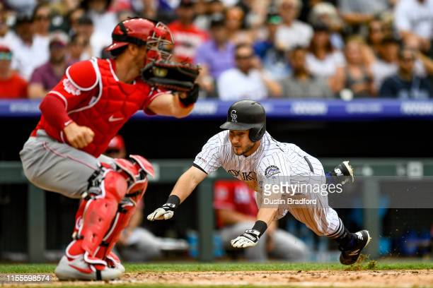 Garrett Hampson of the Colorado Rockies dives to score a fifth inning run ahead of a tag attempt by Kyle Farmer of the Cincinnati Reds at Coors Field...