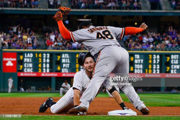 Garrett Hampson of the Colorado Rockies slides into Pablo Sandoval of the San Francisco Giants at third base trying to stretch an RBI double where he...