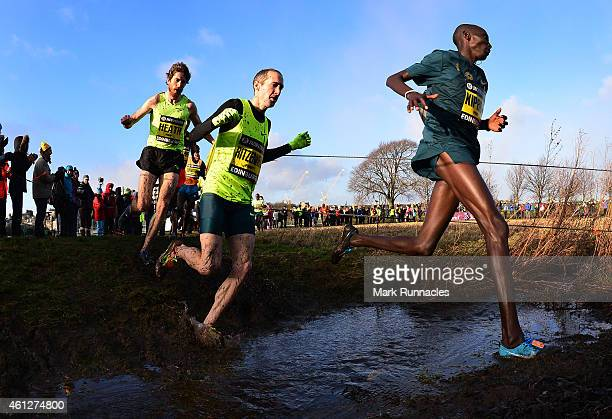 Garrett Heath of USA Dathan Ritzenhein of USA and Abel Kiprop of Kenya crosses a burn as he competes in the invitational menÕs 4k race during the...