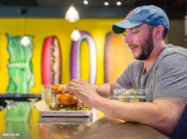 Garrett Jones of Portland reaches for a bacon burger with bbq sauce feta cheese at BRGR Bar on Brown Street in Portland Friday afternoon