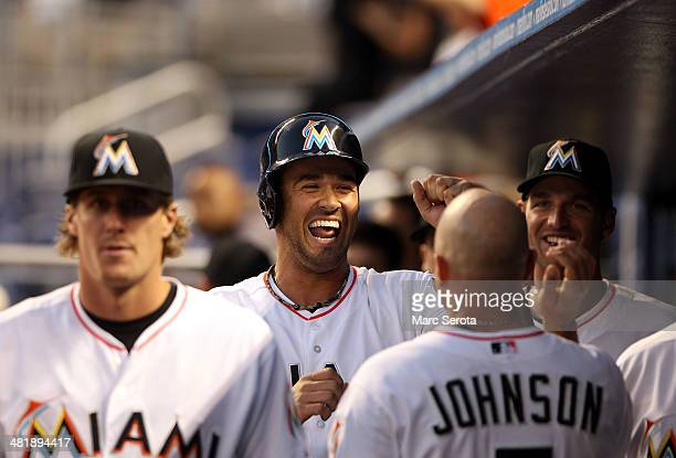 Garrett Jones of the Miami Marlins celebrates scoring a run with teammates against the Colorado Rockies during the third inning at the Marlins Park...