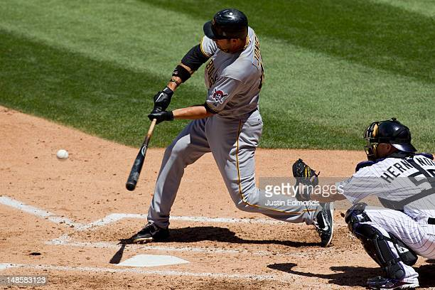 Garrett Jones of the Pittsburgh Pirates hits a threerun home run during the third inning as catcher Ramon Hernandez of the Colorado Rockies looks on...