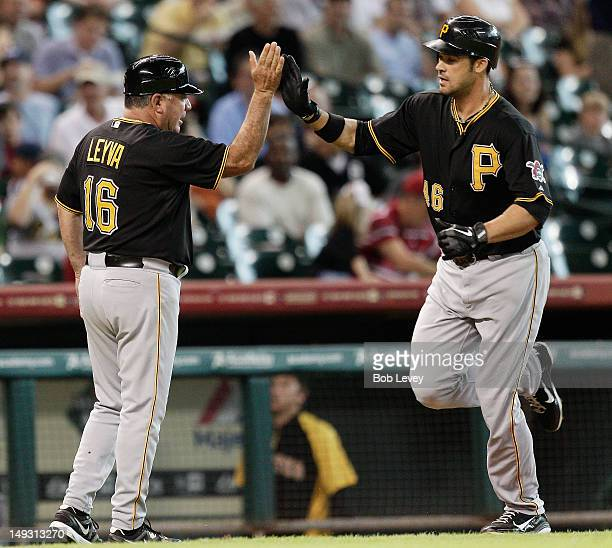 Garrett Jones of the Pittsburgh Pirates receives a high five from third base coach Nick Leyva after hitting a home run in the first inning against...