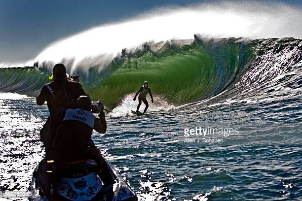 Garrett McNamara, not visible behind the wave, uses a Sea Doo personal water craft to whip 18-year-old TJ Gumiela, of Long Beach, NY, into a large...