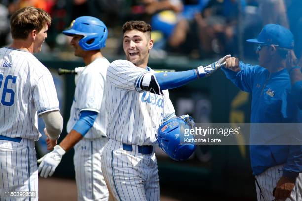 Garrett Mitchell of UCLA fistbumps a coach as he makes his way to the dugout following his home run during a baseball game against University of...