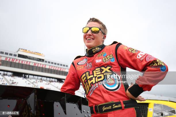 Garrett Smithley driver of the Adapt 2k Chevrolet stands on the grid during qualifying for the NASCAR XFINITY Series Overton's 200 at New Hampshire...