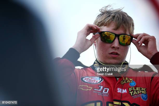 Garrett Smithley driver of the Adapt 2k/Mark Spaulding Construction Chevrolet stands on the grid during qualifying for the NASCAR XFINITY Series...
