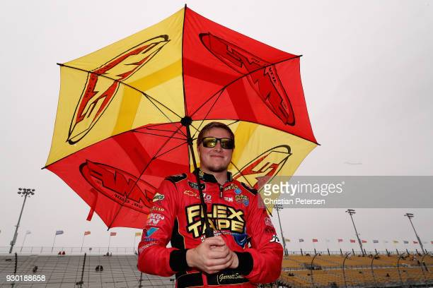 Garrett Smithley driver of the Flex Glue Chevrolet stands on pit road during a red flag for rain during the NASCAR Xfinity Series DC Solar 200 at ISM...