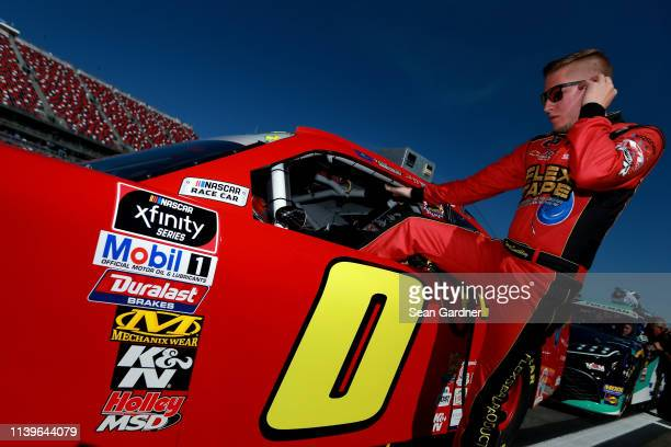 Garrett Smithley driver of the Flex Tape Chevrolet gets into his car during qualifying for the NASCAR Xfinity Series MoneyLion 300 at Talladega...