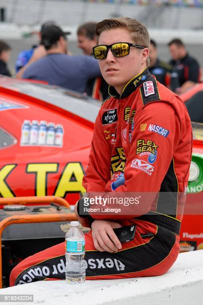 Garrett Smithley driver of the Flex Tape Chevrolet stands by his car during qualifying for the NASCAR Xfinity Series PowerShares QQQ 300 at Daytona...