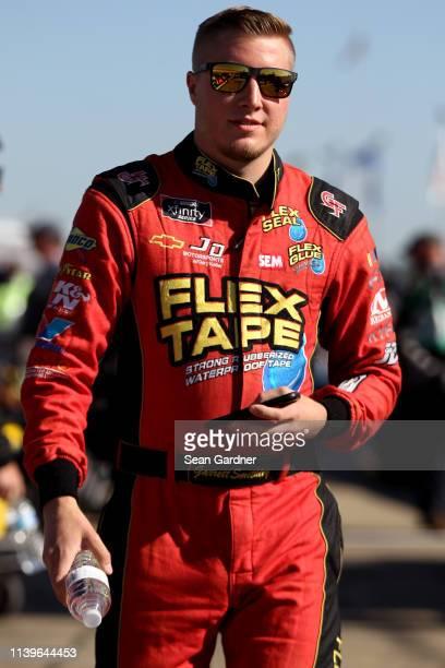 Garrett Smithley driver of the Flex Tape Chevrolet walks on the grid during qualifying for the NASCAR Xfinity Series MoneyLion 300 at Talladega...