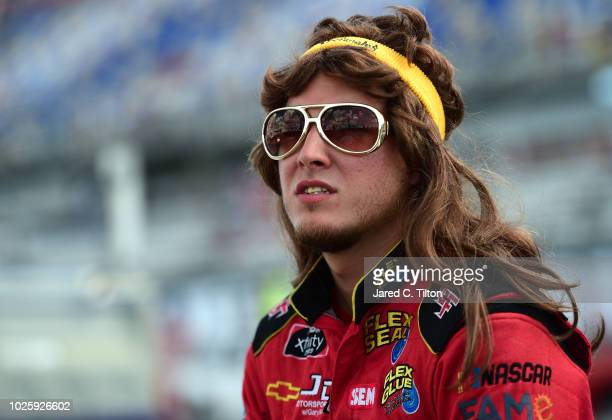 Garrett Smithley driver of the South Carolina Education Lottery Chevrolet stands on the grid prior to the NASCAR Xfinity Series Sport Clips Haircuts...