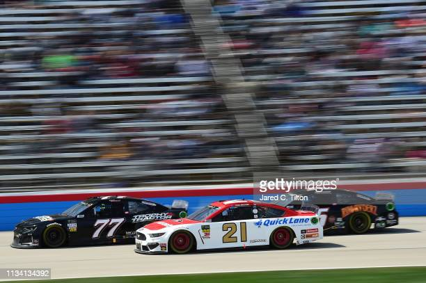 Garrett Smithley driver of the Trophy Tracker Chevrolet races Paul Menard driver of the Motorcraft/Quick Lane Tire Auto Center Ford and Ross Chastain...