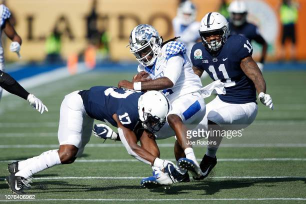 Garrett Taylor and Micah Parsons of the Penn State Nittany Lions tackle Terry Wilson of the Kentucky Wildcats in the first quarter of the VRBO Citrus...