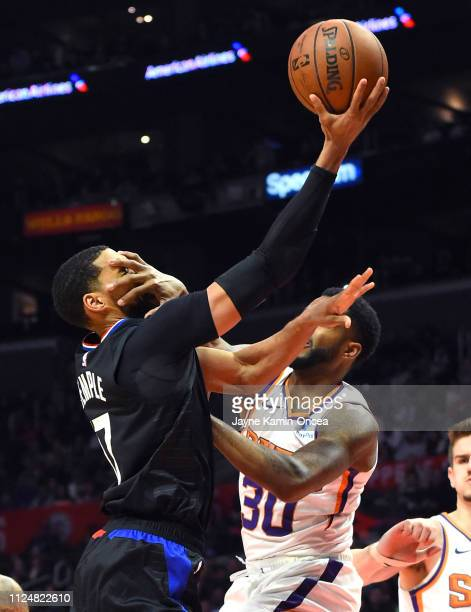 Garrett Temple of the Los Angeles Clippers is fouled by Troy Daniels of the Phoenix Suns as he drives to the basket in the second half of the game at...