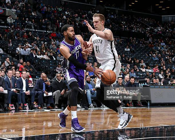Garrett Temple of the Sacramento Kings passes the ball around Justin Hamilton of the Brooklyn Nets on November 27 2016 at Barclays Center in Brooklyn...