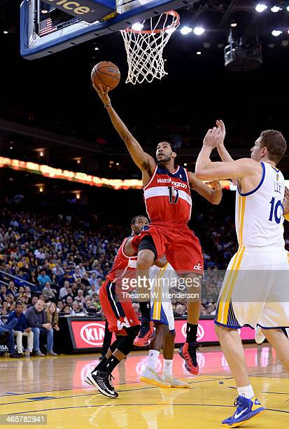 Garrett Temple of the Washington Wizards goes in for a layup over David Lee of the Golden State Warriors at ORACLE Arena on January 28 2014 in...