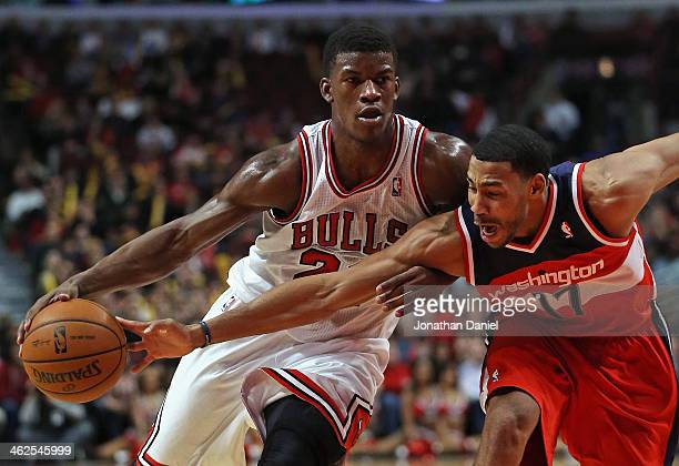 Garrett Temple of the Washington Wizards tries to knock the ball away from Jimmy Butler of the Chicago Bulls at the United Center on January 13 2014...