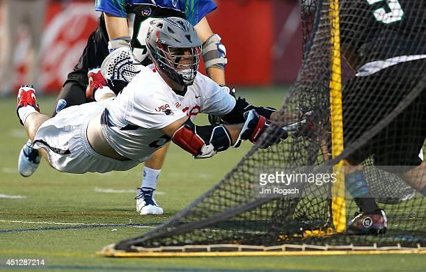 Garrett Thul of Team USA scores on Jordan Burke of Team MLL in the second quarter during the 2014 MLL All Star Game at Harvard Stadium on June 26...