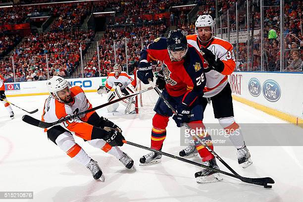 Garrett Wilson of the Florida Panthers tangles with Mark Streit and teammate PierreEdouard Bellemare of the Philadelphia Flyers at the BBT Center on...