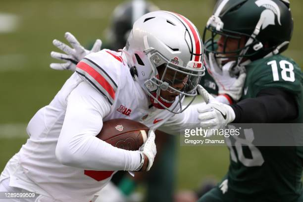 Garrett Wilson of the Ohio State Buckeyes gets around the tackle of Kalon Gervin of the Michigan State Spartans to score a first half touchdown at...