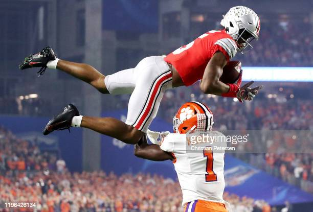 Garrett Wilson of the Ohio State Buckeyes is tackled by Derion Kendrick of the Clemson Tigers after making a first down catch in the first half...