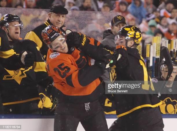 Garrett Wilson of the Pittsburgh Penguins goes up against James van Riemsdyk of the Philadelphia Flyers during the 2019 Coors Light NHL Stadium...