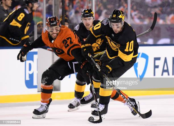 Garrett Wilson of the Pittsburgh Penguins tries to play the puck as Justin Bailey of the Philadelphia Flyers goes for the poke check during the first...