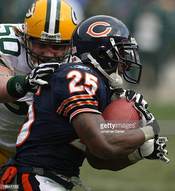 Garrett Wolfe of the Chicago Bears tries to break away from AJ Hawk of the Green Bay Packers on December 23 2007 at Soldier Field in Chicago Illinois