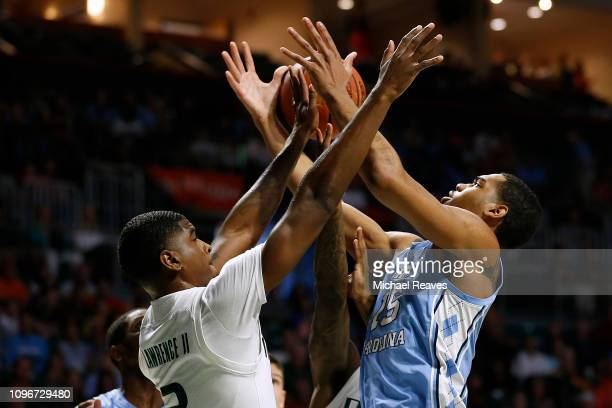 Garrison Brooks of the North Carolina Tar Heels is fouled by Anthony Lawrence II of the Miami Hurricanes at Watsco Center on January 19 2019 in Miami...