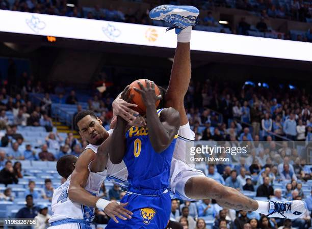 Garrison Brooks of the North Carolina Tar Heels lands on Eric Hamilton of the Pittsburgh Panthers as they battle for a rebound during the first half...