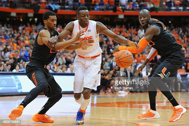 Garrius Adams of the Miami Hurricanes Jerami Grant of the Syracuse Orange and Tonye Jekiri of the Miami Hurricanes battle for a loose ball during the...