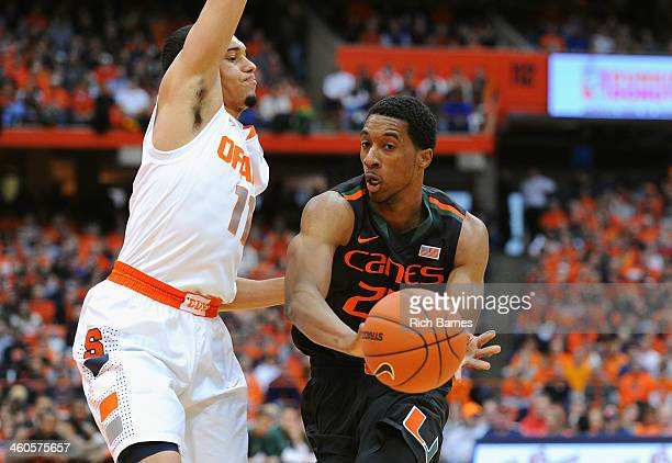 Garrius Adams of the Miami Hurricanes passes the ball around the defense of Tyler Ennis of the Syracuse Orange during the first half at the Carrier...
