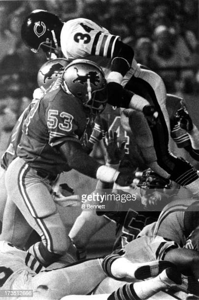 Garry Cobb of the Detroit Lions tries to tackle Walter Payton of the Chicago Bears during an NFL game circa 1982 at the Pontiac Silverdome in...