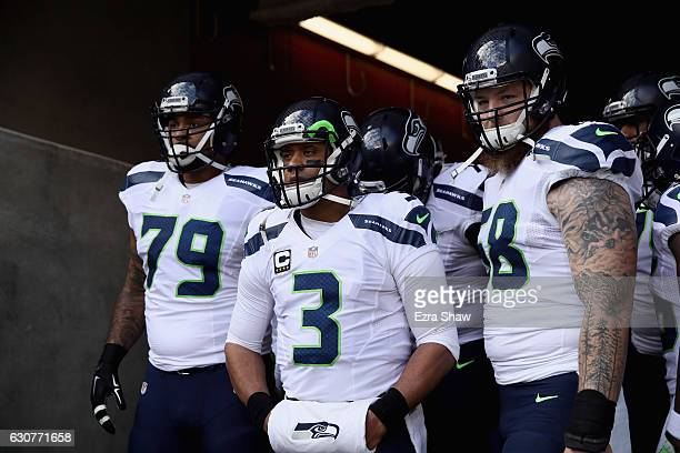 Garry Gilliam Russell Wilson and Justin Britt of the Seattle Seahawks get ready to run on to the field for their game against the San Francisco 49ers...