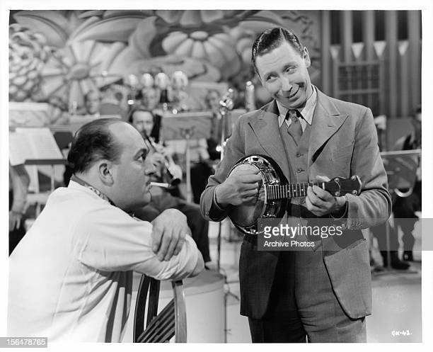 Garry Marsh watching George Formby play the banjo in a scene from the film 'To Hell With Hitler' 1940