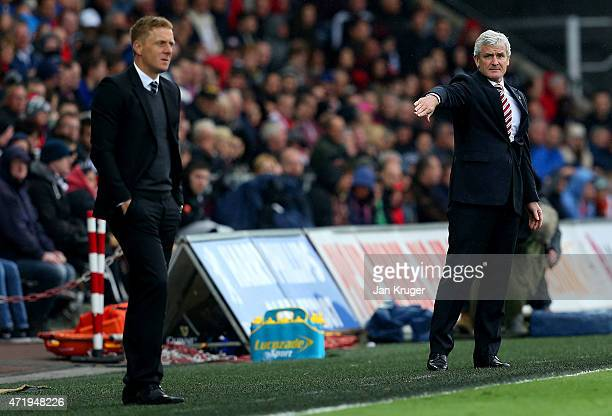 Garry Monk manager of Swansea City and manager Mark Hughes of Stoke City look on during the Barclays Premier League match between Swansea City and...