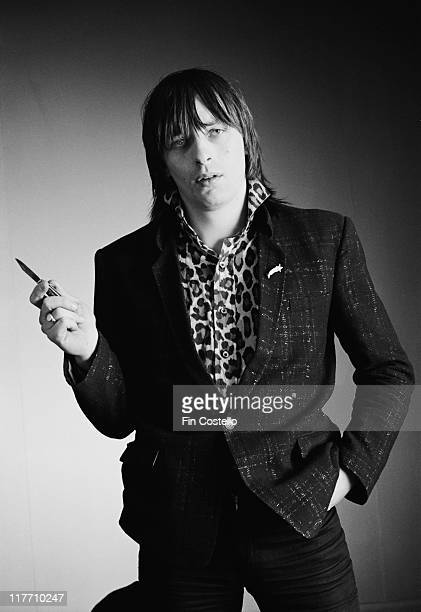 Garry Roberts guitarist with Irish punk band The Boomtown Rats wearing a leopardprint shirt and holding a penknife in a studio portrait in February...