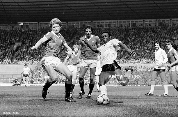 Garth Crooks of Tottenham Hotspur shoots watched by defenders Gordon McQueen and John Gidman of Manchester United during their Division One match at...